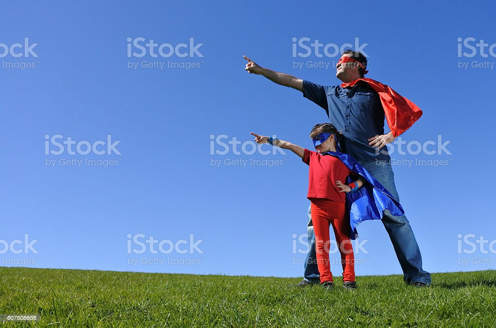 Superhero father shows his daughter how to be  a superhero stock photo