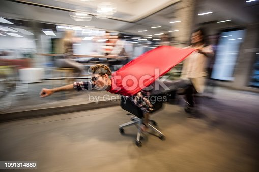 Playful creative people having fun on a break at casual office while man on a chair is pretending to be a superman. Blurred motion.