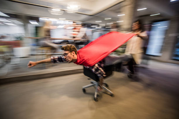 Superhero in the office! Playful creative people having fun on a break at casual office while man on a chair is pretending to be a superman. Blurred motion. heroes stock pictures, royalty-free photos & images