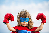 Superhero kid wearing boxing gloves against blue sky background. Girl power and feminism concept