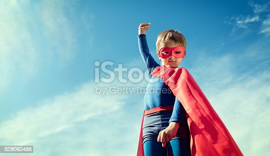 istock Superhero kid in red cape and mask 528060486