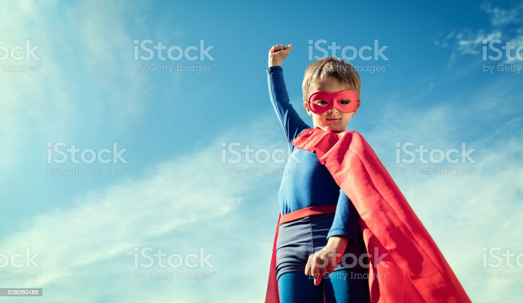 Superhero kid in red cape and mask stock photo