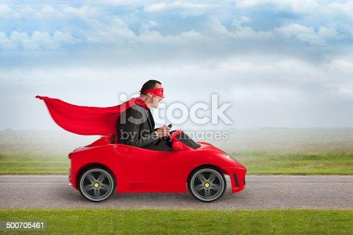 1035136022 istock photo superhero man driving a toy racing car 500705461