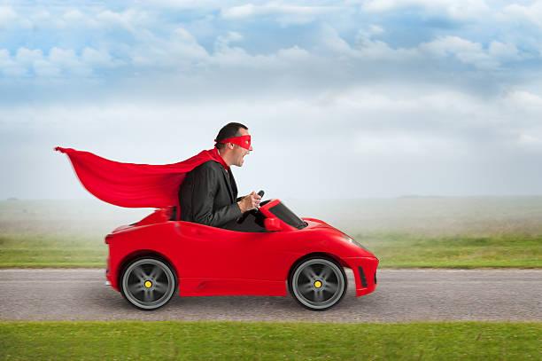 superheld mann ein spielzeug rennen auto fahren - 1m coupe stock-fotos und bilder