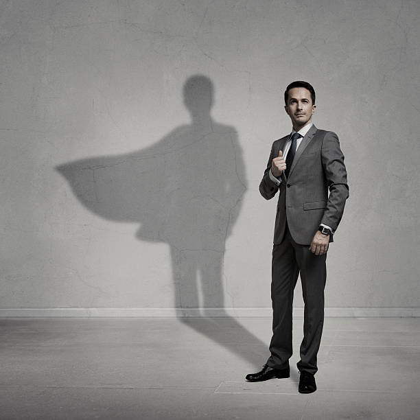 Superhero Businessman with a superhero shadow on the wall heroes stock pictures, royalty-free photos & images