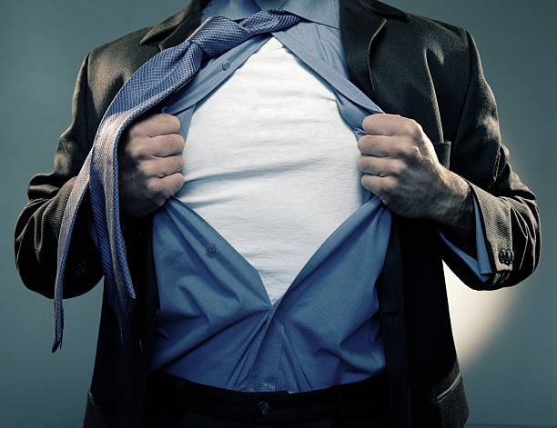 Superhero Pulling Open Shirt in Mid Air A cross processed image of the torso of a male Caucasian man dressed in a smart business suit, blue shirt and tie pulling his shirt open in a superhero changing pose, to reveal a white t shirt where text can be added. The superhero is standing against a dark blue green background.  fully unbuttoned stock pictures, royalty-free photos & images