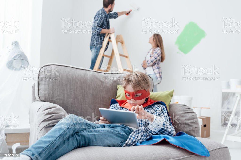 Superhero using a tablet and home makeover Стоковые фото Стоковая фотография