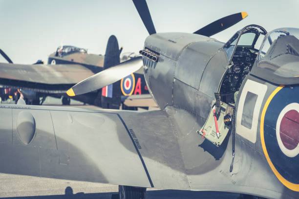 supermarine spitfire with an avro lancaster bomber in the background - airshow stock photos and pictures
