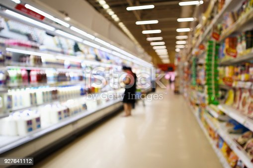 836871040 istock photo Supermarket Aisle and Shelves with dairy products in refrigerator blur background 927641112