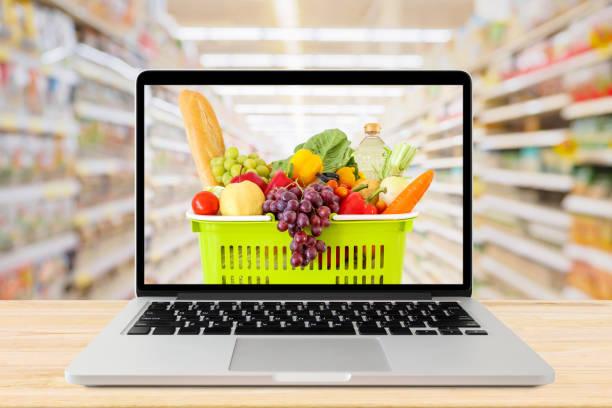 Supermarkt Gang verschwommenen Hintergrund mit Laptop-Computer und Einkaufskorb auf Holz Tisch Lebensmittel Online-Konzept – Foto