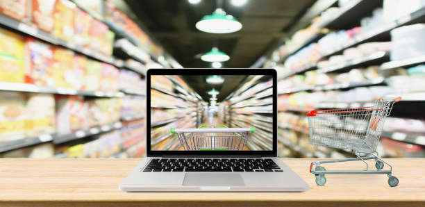 supermarket aisle blurred background with laptop computer and cart on wood table online shopping concept - icona supermercato foto e immagini stock