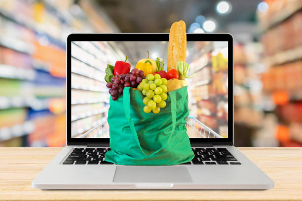 supermarket aisle blurred background with laptop computer and green shopping bag on wood table grocery online concept - prodotti supermercato foto e immagini stock