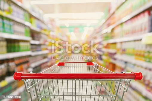 Supermarket aisle interior blur background with empty red shopping cart