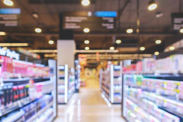 supermarket aisle with cosmetic healthcare product shelves interior defocused blur background - prodotti supermercato foto e immagini stock