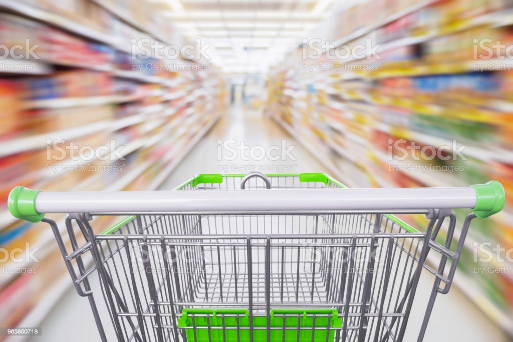 Supermarket aisle with empty green shopping cart in motion - Royalty-free Abstract Stock Photo
