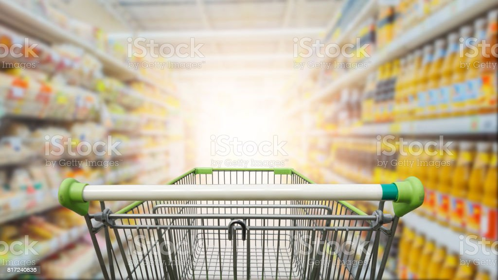 Supermarket aisle with empty green shopping cart stock photo