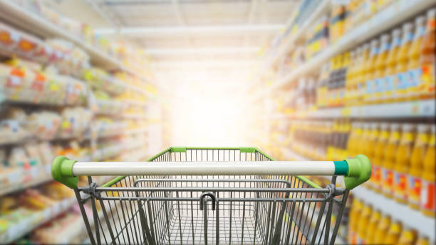 supermarket aisle with empty green shopping cart - shopping stock photos and pictures