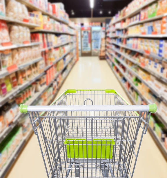 Supermarket aisle with empty shopping cart business concept Supermarket aisle with empty shopping cart business concept grocery aisle stock pictures, royalty-free photos & images