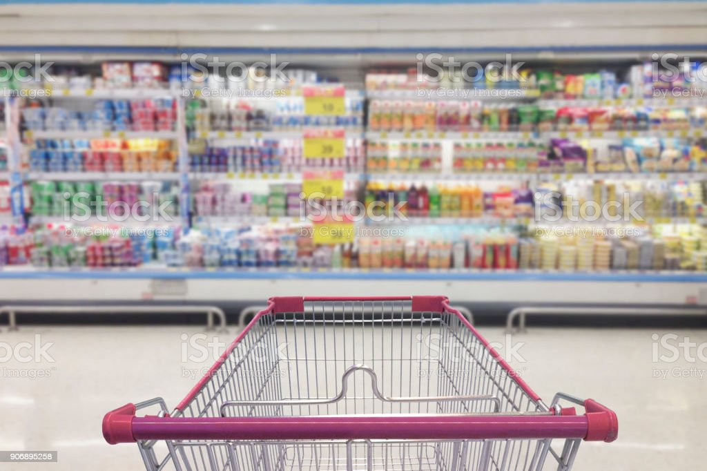 Supermarket aisle with empty shopping cart stock photo