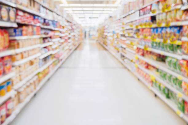 Supermarket aisle with product shelves abstract blur defocused background Supermarket aisle with product shelves abstract blur defocused background snack aisle stock pictures, royalty-free photos & images