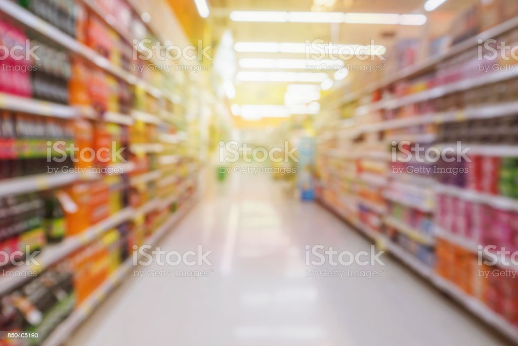 supermarket aisle with soft drink bottles product shelves blurred background stock photo
