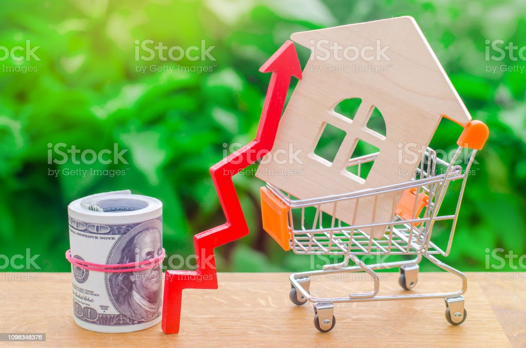 A supermarket cart with a small house and a wooden arrow up on a green background. The rise of prices for property . Increase in demand for housing in the primary market. fall in prices. banner stock photo