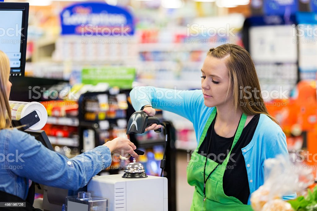 Supermarket cashier scanning smart phone to accept payment stock photo