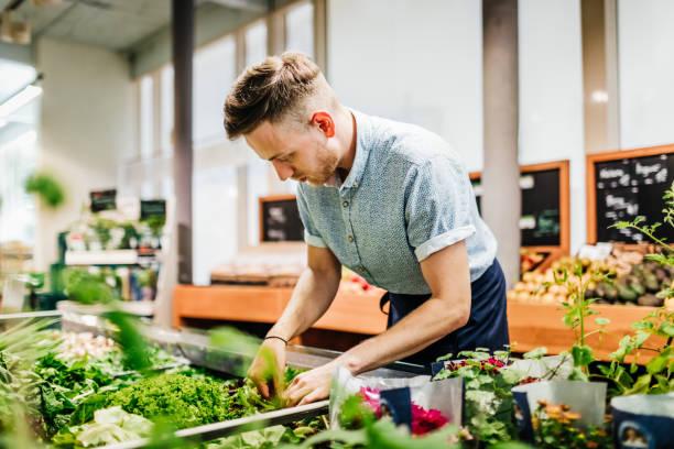 Supermarkt-Angestellter arrangieren Lebensmittel während der Arbeit – Foto