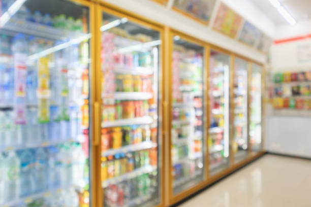 supermarket convenience store refrigerators with soft drink bottles on shelves abstract blur background stock photo