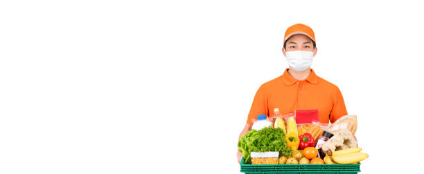 Supermarket delivery man wearing medical mask while holding food and groceries basket isolated on white banner background with copy space stock photo