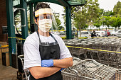 Supermarket employee wearing masks and latex gloves due contagion prevention posing with his arms crossed at the Supermarket entrance