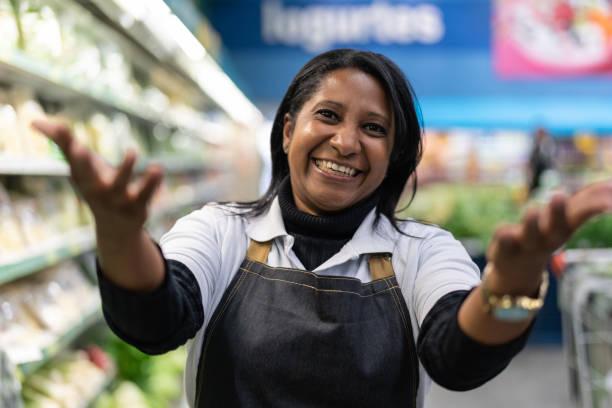 mulher de funcionário do supermercado acenando - convidando clientes para vir - vem - fotografias e filmes do acervo