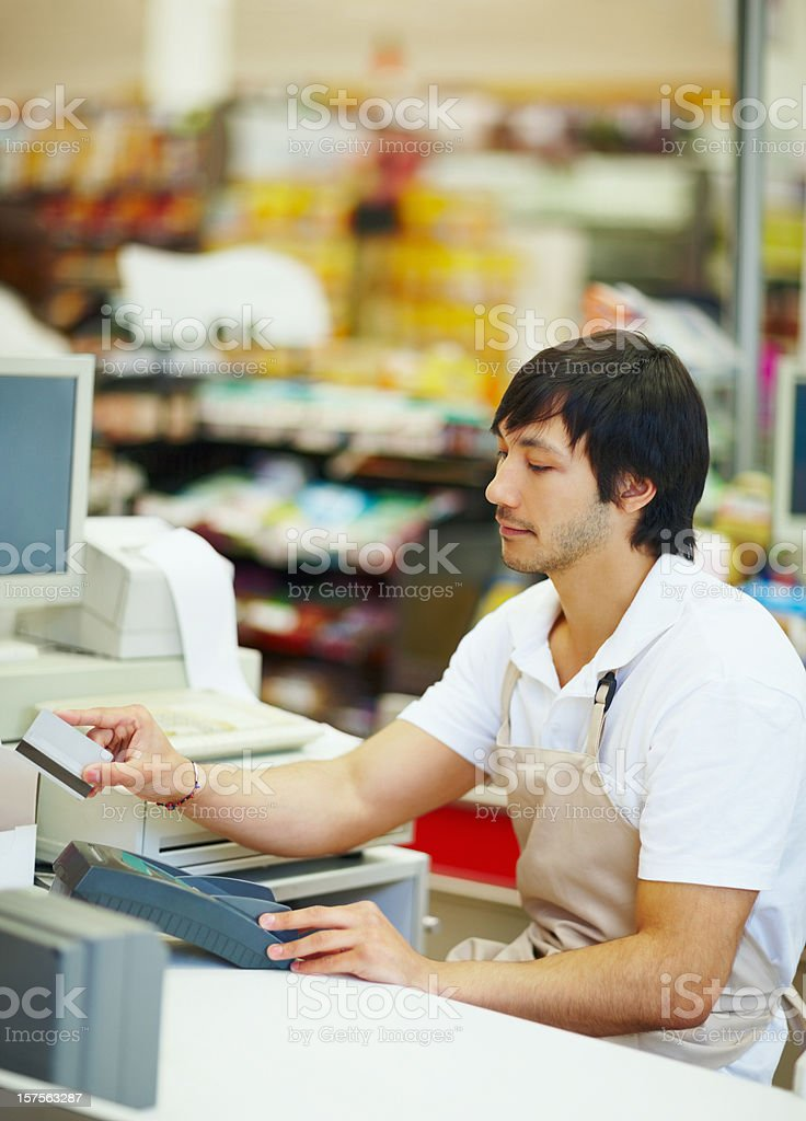 Supermarket employee working at the cashpoint royalty-free stock photo