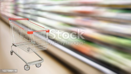 922721264 istock photo supermarket grocery store with fruit and vegetable shelves interior defocused background with empty red shopping cart 1027589116