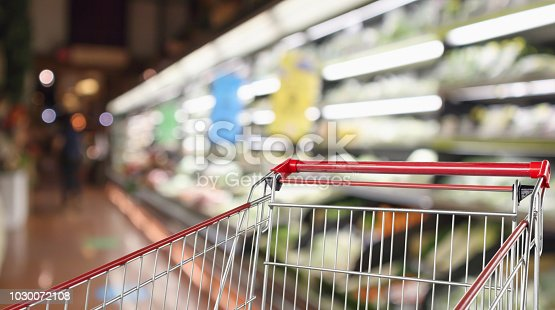 922721264 istock photo supermarket grocery store with fruit and vegetable shelves interior defocused background with empty red shopping cart 1030072108