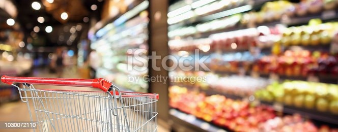 922721264 istock photo supermarket grocery store with fruit and vegetable shelves interior defocused background with empty red shopping cart 1030072110
