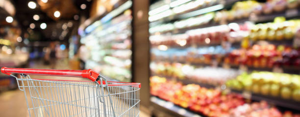 supermarket grocery store with fruit and vegetable shelves interior defocused background with empty red shopping cart - prodotti supermercato foto e immagini stock