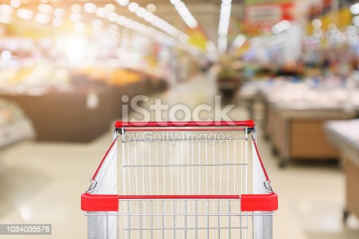 922721264 istock photo supermarket grocery store with fruit and vegetable shelves interior defocused background with empty red shopping cart 1034035578