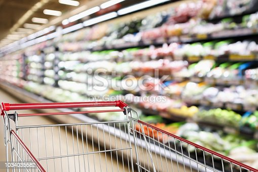 922721264 istock photo supermarket grocery store with fruit and vegetable shelves interior defocused background with empty red shopping cart 1034035582