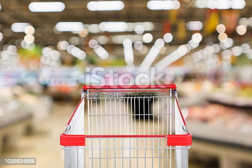 922721264 istock photo supermarket grocery store with fruit and vegetable shelves interior defocused background with empty red shopping cart 1035834856