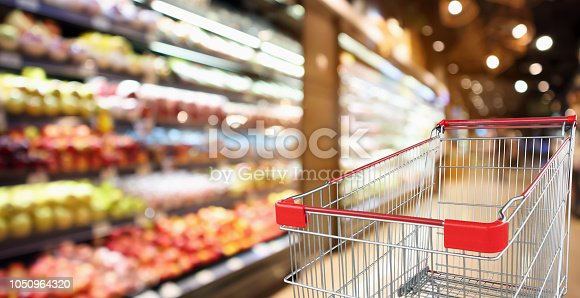 922721264 istock photo supermarket grocery store with fruit and vegetable shelves interior defocused background with empty red shopping cart 1050964320