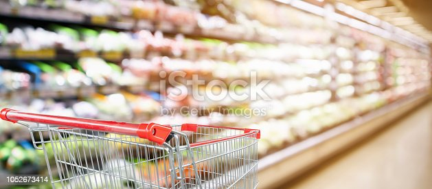 922721264 istock photo supermarket grocery store with fruit and vegetable shelves interior defocused background with empty red shopping cart 1052673414
