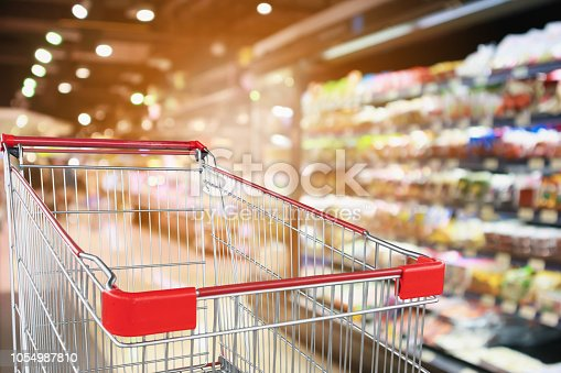 922721264 istock photo supermarket grocery store with fruit and vegetable shelves interior defocused background with empty red shopping cart 1054987810