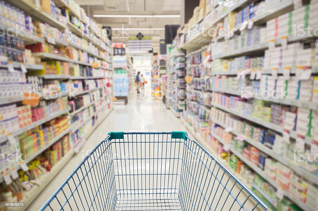 Supermarket interior, empty green shopping cart stock photo