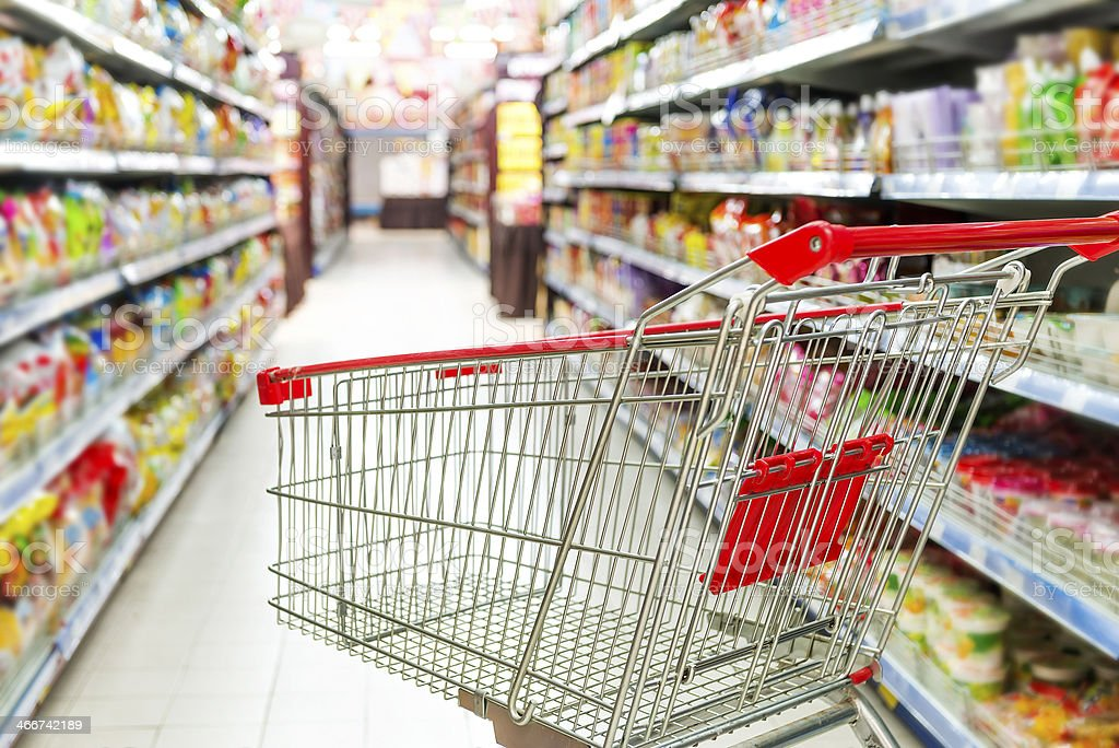 Supermarket interior, empty red shopping cart. stock photo