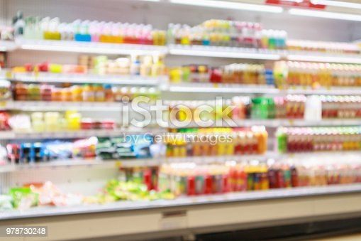 922721264 istock photo Supermarket refrigerator shelves with fruit juice soft drink product abstract blur background 978730248
