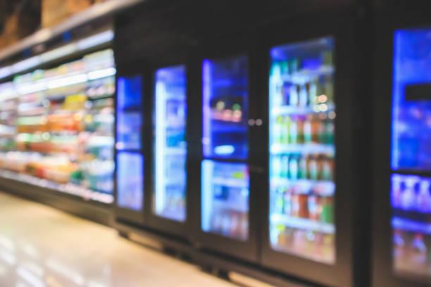 supermarket refrigerators with soft drink bottles on shelves abstract blur background - prodotti supermercato foto e immagini stock