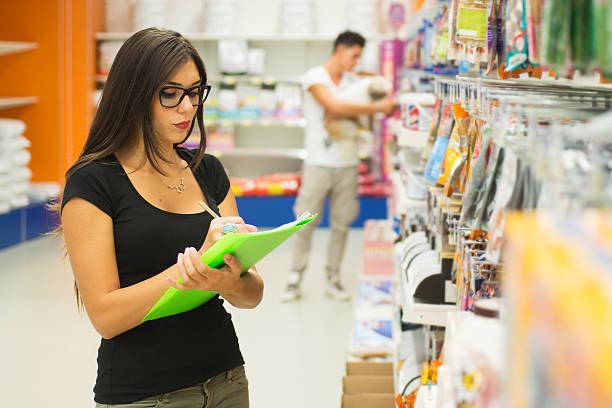 Supermarché Employé de magasin vérifiant les produits.  Client avec chien sur fond - Photo