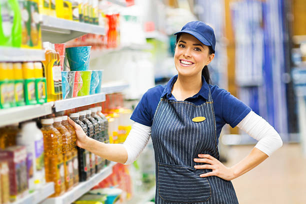 supermarket saleswoman standing in store stock photo