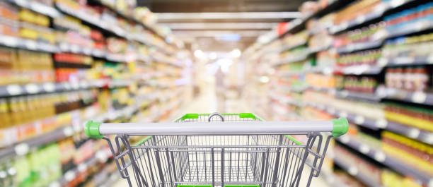supermarket shelves aisle with empty shopping cart defocused interior blur bokeh light background supermarket shelves aisle with empty shopping cart defocused interior blur bokeh light background aisle stock pictures, royalty-free photos & images